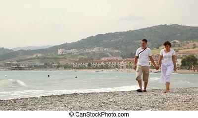 Enamoured walk slowly keeping for hands on sea coast