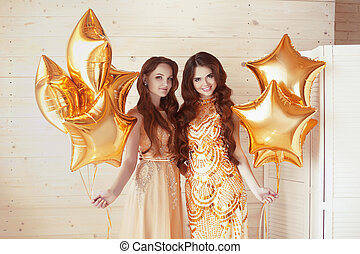 encantador, damas, fiesta, dos mujeres, en, moda, dorado, vestidos, con, brillante, estrellas, balloons., celebration., feliz cumpleaños, fondo.