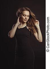 encantador, morena, modelo, en, vestido negro, con, ondear, pelo, con, viento