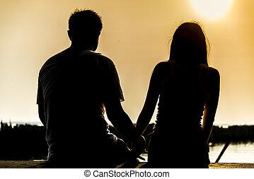 encantador, pareja, sentarse, en, el, ocaso, con, silueta,...