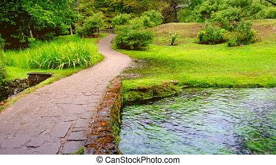 enchanted eden garden bridge over pond in horizontal panning...