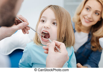 Enchanting girl showing her teeth to doctor