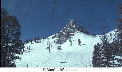 Enclosed chairlifts zoom past on blue sky day