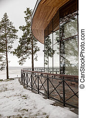 enclosed glass terrace of modern restaurant on lake shore in beautiful winter snow. Architecture, modern building, view to the terrace. snowy patio with glass balustrades, in the background trees and snow landscape.