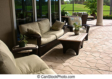 Large enclosed outdoor living atea with outside furniture and golf course in background in southwest florida