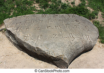 Encoded ancient engraved inscription by Gothic font with missing letters on a large boulder