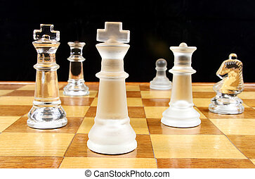 End Game - Glass Chess Pieces on a wooden chessboard