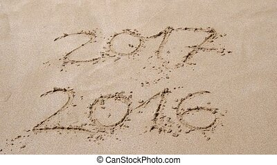 End of 2016, beginning of 2017 written in the sand on the...