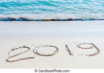 End of 2019 handwritten on the sandy beach with ocean wave washing away with water.. Happy new year 2020 concept.