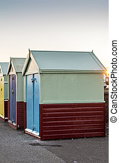 End of a row of colourful wooden beach huts