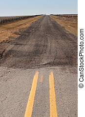 the end of the paved road where it turns into a gravel road extending to the horizon