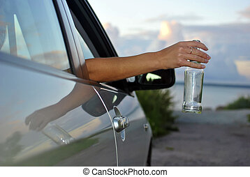 end of the evening: a woman's hand holding an empty bottle from the car window