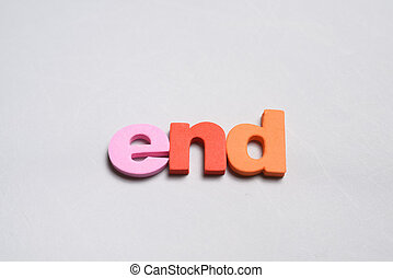 End, word written on white background with colorful polystyrene letters.