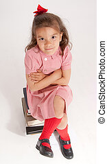 Endearing little girl on a pile of books