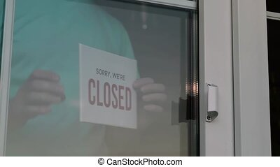 Close up of the male Caucasian hands turning a signboard on the glass door of the shop from CLOSED to OPEN. Reopening of a small business activity after quarantine covid-19 emergency.