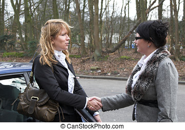 Ending a businessmeeting - Two business women shaking each ...