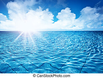 Endless pool water with blue sky background and bright sun...