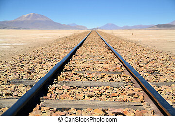 Endless train tracks in the desert with a volcano in the...