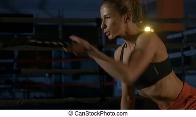 Endurance. Muscular woman with rope in crossfit gym
