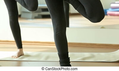 Young women doing yoga exercise standing still and testing their endurance