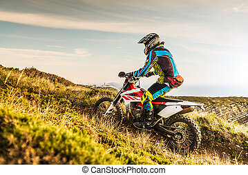 Enduro rider climbing a steep slope against a sunset sky.