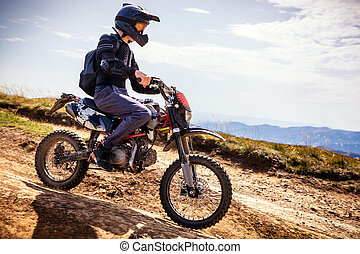 Enduro biker crossing road at high speed in Carpathian mountains.