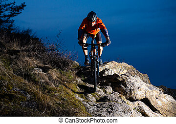 Enduro Cyclist Riding the Bike on the Rock at Night. Extreme Sport Concept. Space for Text.