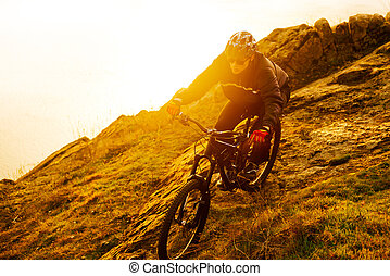 Enduro Cyclist Riding the Mountain Bike Down Beautiful Rocky Trail. Extreme Sport Concept. Space for Text.