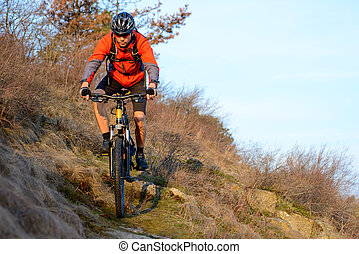 Enduro Cyclist Riding the Mountain Bike on the Rocky Trail. Extreme Sport Concept. Space for Text.