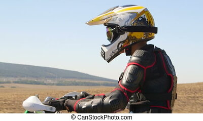Enduro racer in motorcycle protective gear riding dirt bike closeup