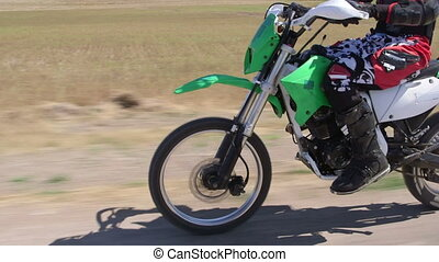 Enduro racer in motorcycle protective gear riding dirt bike,...