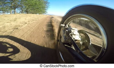 Enduro racer riding bike on dirt track kicking up dust rear wheel point of view