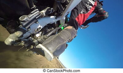 Enduro racer riding bike on dirt track rear wheel point of view