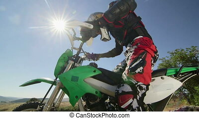Enduro racer starting engine of his dirt bike riding away against sun