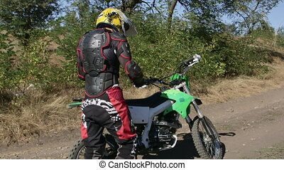 Enduro racer starting engine of his motorbike riding away on dirt track