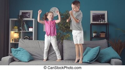 Energetic brother and sister jumping together on couch - ...