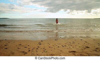 Energetic brunette running into the ocean