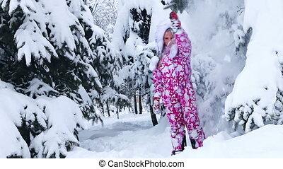 Energetic child in winter snow outdoor on walk. Girl go in...