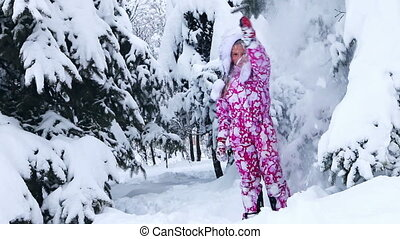 Energetic child in winter snow outdoor on walk. Girl go in...