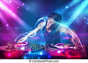 Energetic Dj mixing music with powerful light effects