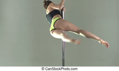 Energetic Elegance - Fit young lady moving around the pole...