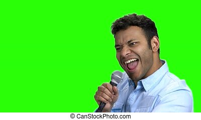 Energetic entertainer talking into microphone on green screen.