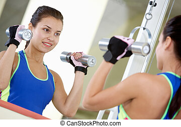 Energetic exercise - Portrait of young female with dumbbells...