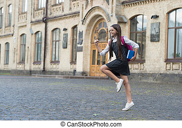 Energetic happy kid hurry to school in uniform with book carrying backpack outdoors, back to school, copy space.