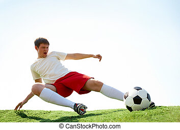 Energetic kick - Portrait of soccer player kicking ball...