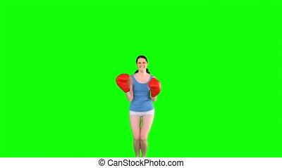 Energetic model in sportswear jumping on green background