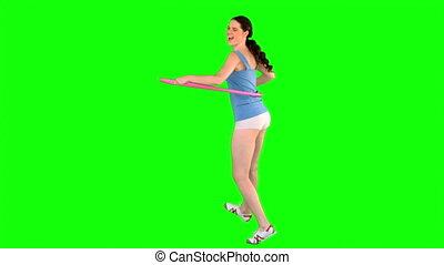 Energetic model in sportswear using hoop while posing on...