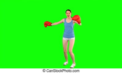 Energetic model with boxing gloves spinning round on green...