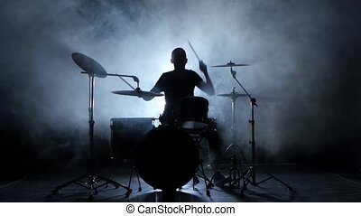 Energetic music in the performance of a professional drummer. Black background. Silhouette