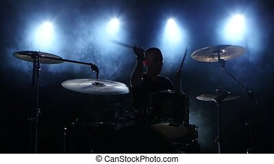 Energetic music in the performance of a professional drummer. Black smoky background. Silhouette